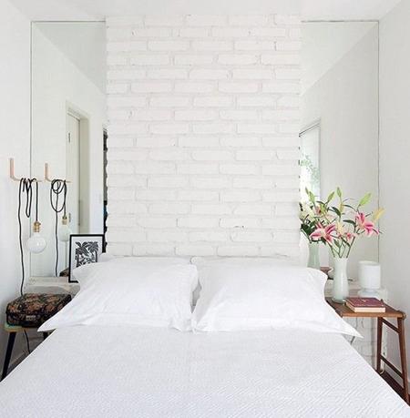 Bức tường gạch độc đáo kết hợp với gương tạo cảm giác rộng rãi cho phòng ngủ